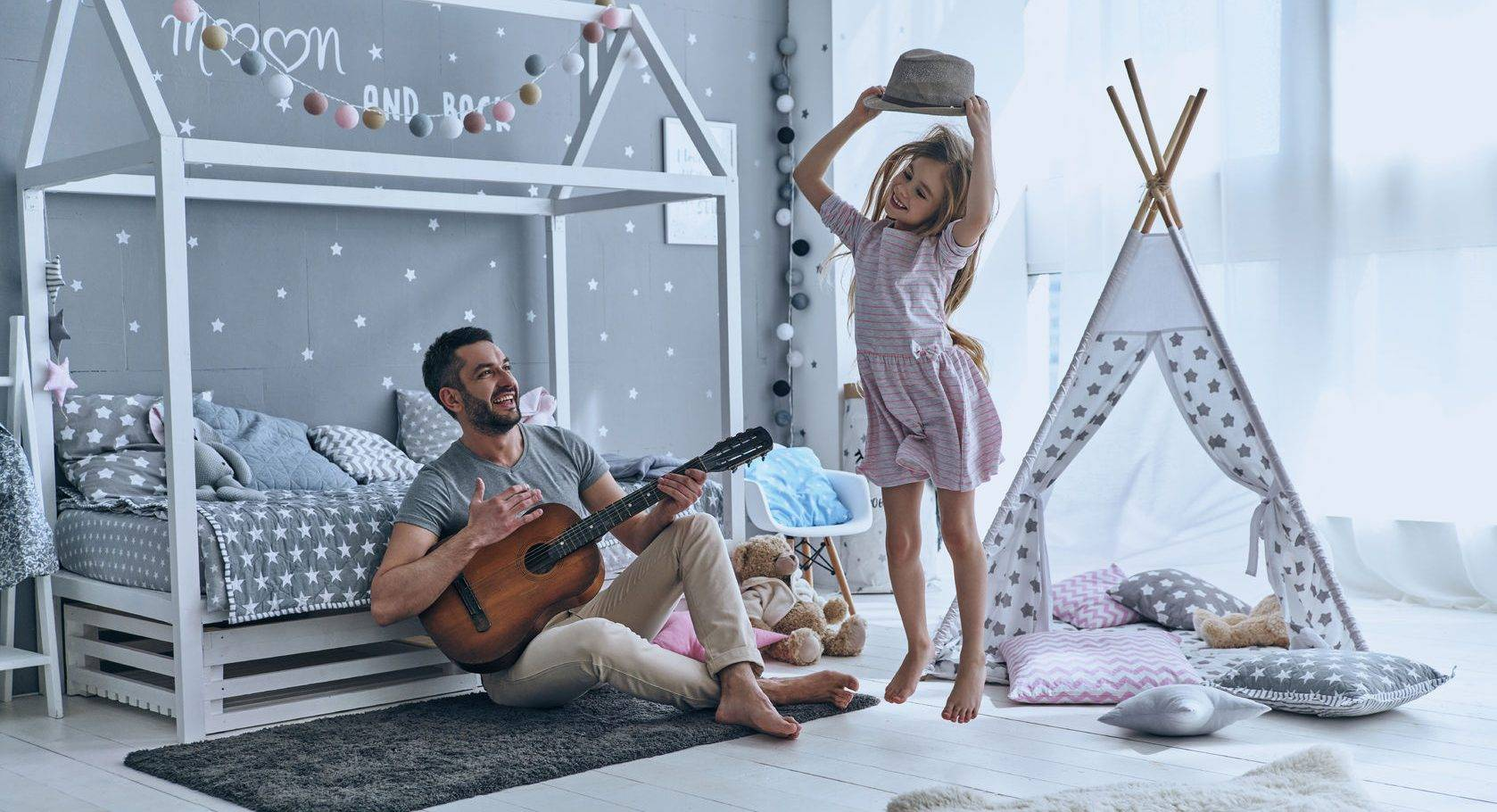 Young father plays guitar for his little daughter while she is jumping in bedroom, displaying her unique identity.