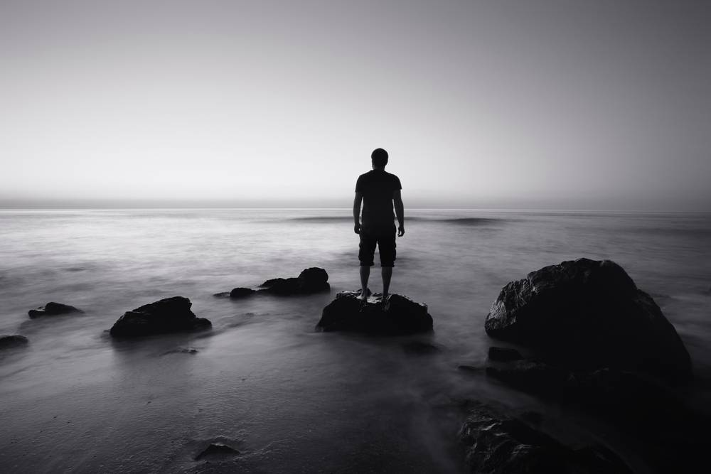 A call to all good men: man standing on rock in front of ocean