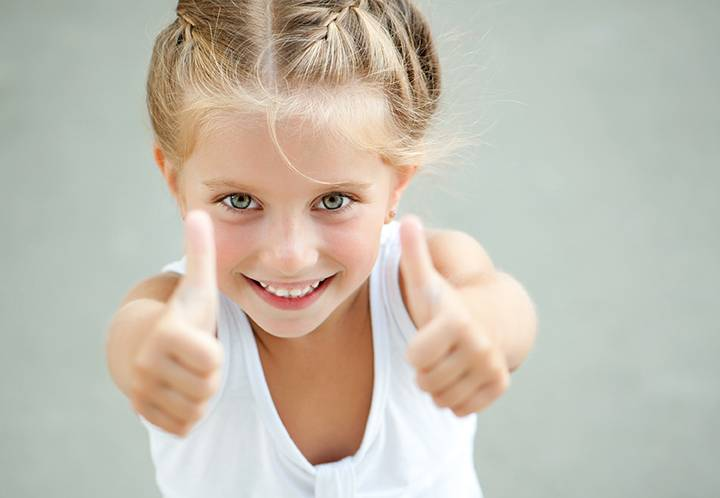 How to build your child's self esteem: little girl gives thumbs up